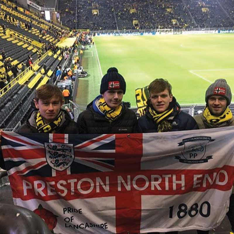 Four lads on the terrace holding their own Preston North End personalised flag designed online
