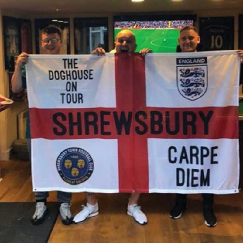 Three lads in the pub holding Shrewsbury St George Cross custom designed flag Carpe Diem