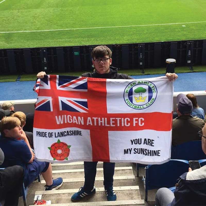 A lad on the terrace holding Wigan Athletic St George Cross flag