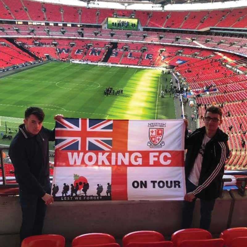 Two lads on the terrace holding Woking FC On Tour personalised outdoor banner