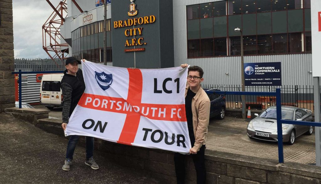 Two lads holding Portsmouth flag just outside Bradford City stadium